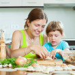 woman with child cooking fish pelmeni (pelmeni), today together — Stock Photo