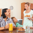 Woman serves croissants  her husband and son   — Stock Photo