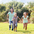 Family of three running on grass — Stock Photo