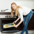 Long-haired girl cooking fish in oven  — Stock Photo