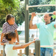parents with child  training with pull-up bar   — Stock Photo