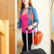 Cute positive woman in jeans with luggage leaving the home — Stock Photo