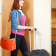 Smiling female tourist with luggage near door in home — Stock Photo