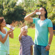 Parents with teenager drinking from  bottles  — Stock Photo