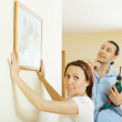 Couple choosing point for picture on wall at home — Stock Photo