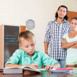 Parents watching their son doing homework — Stock Photo