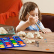 The child learns to paint the dough figurines — Stock Photo