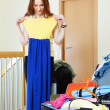 Woman choosing dress for vacation — Stock Photo