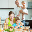 Family of four together in the kitchen prepares healthy food — Stock Photo