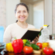 Mature housewife reads cookbook for recipe — Stok fotoğraf