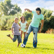 Happy family of three playing with  ball  — Stockfoto