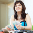 Stock Photo: Happy girl calculates family budget