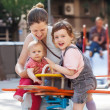Happy woman children on swings — Stock Photo #35143849