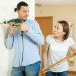 Stock Photo: Man and woman hanging art picture at home