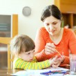 Foto Stock: Mother and child drawing on paper with hand printing