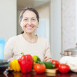 Smiling mature housewife cooking veggie lunch   — Stock fotografie