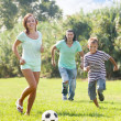 parents with teenager son playing with soccer ball   — Stok fotoğraf