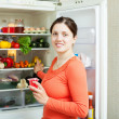 Young woman near fridge — Stock Photo