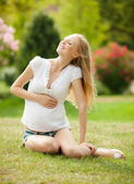 Pregnant woman relaxing on grass — Stock Photo