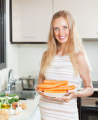 Happy pregnant woman holding carrots — Stok fotoğraf