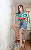 Kız boya duvar ev — Stok fotoğraf