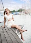 Mujer embarazo sentada en el mar puerto — Foto de Stock