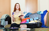 Woman sitting on sofa and packing suitcase — ストック写真