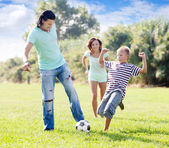 Family with teenager child playing with soccer ball — Stockfoto