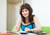 Serious housewife fills in utility payments bills — Stock Photo