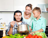 Happy family of three cooking lunch — Stock Photo