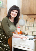 Happy housewife cleans the gas-stove with sponge — Foto Stock