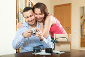 Middle-aged couple with new digital camera at home — Stock Photo