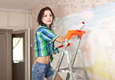 Woman paints wall with roller — Photo