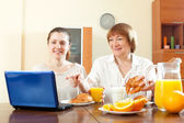 Women looking e-mail in laptop during breakfast — Stock Photo