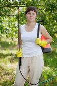 Woman holding garden spray — Stock Photo