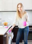 Woman putting whitener in to washing machine — Stock Photo