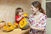 Happy mother with child cooks pumpkin — Stock Photo