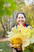 Laughing mature woman in autumn park — Stock Photo