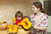 Mother with child cooks pumpkin — Stock Photo