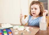 A child paints a dough figurines — Stock Photo