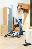 Happy long-haired woman with vacuum cleaner — Stock Photo