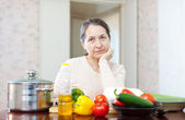 Pensive mature woman with vegetables — Stock Photo