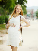 Pregnancy woman against summer street — Stock Photo