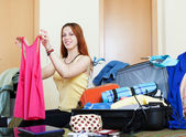 Female traveler packing suitcase at home — Stock Photo