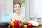 Smiling mature housewife cooking veggie lunch — Stock Photo
