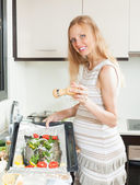 Pregnancy woman cooking trout fish — Stockfoto