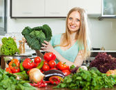Happy housewife with raw cabbage and vegetables — Stock Photo