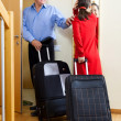 Happy mature couple with suitcases looking in mirror — Stock Photo #38497641