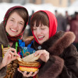 Girls tasting pancake during Shrovetide — Stock Photo #38497789