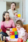 Mature woman and her adult daughter plays with children — Stock Photo